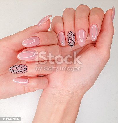 istock Beautiful pink manicure with leopard design. Female fingers with long round nails and pink gel polish 1284429640