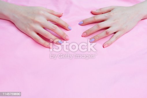 istock Beautiful Pink Nail Polish. Female Hands with Pink Nails Manicure on Pink Fabric Background Great for Any Use. 1145759690