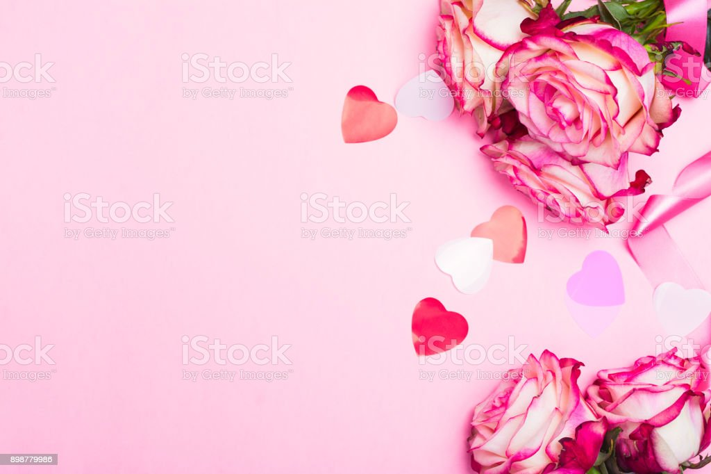 Beautiful pink rose, decorative confetti hearts and pink ribbon on pink Valentines day background royalty-free stock photo