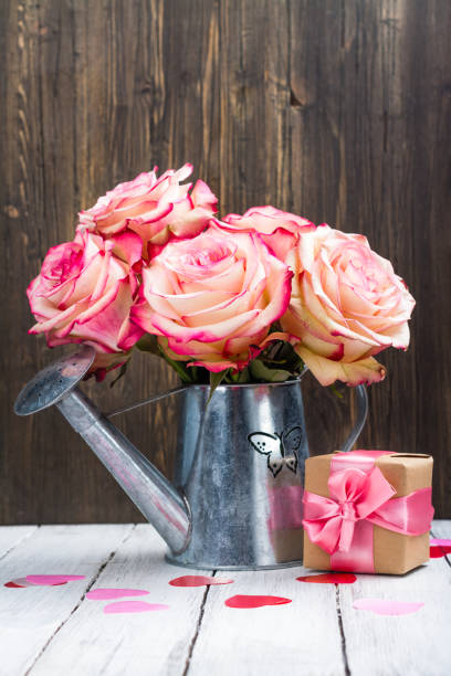 schöne rosa rose in einer zinn gießkanne auf hölzernen hintergrund - zinn hochzeit stock-fotos und bilder