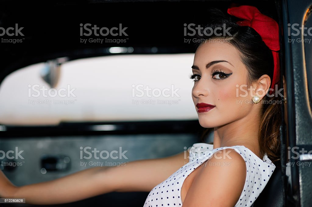 Beautiful pin-up portrait inside vintage car stock photo
