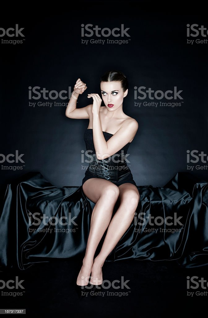 Beautiful Pinup Young Woman in Black Corset on Silk, Copyspace stock photo
