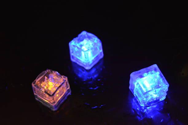 schöne kunststoff glühende eiswürfel auf einem glänzenden schwarzen hintergrund. ruhediode beleuchtung blau und gelb mit einem funkelnden effekt. - birnen verlobungsringe stock-fotos und bilder