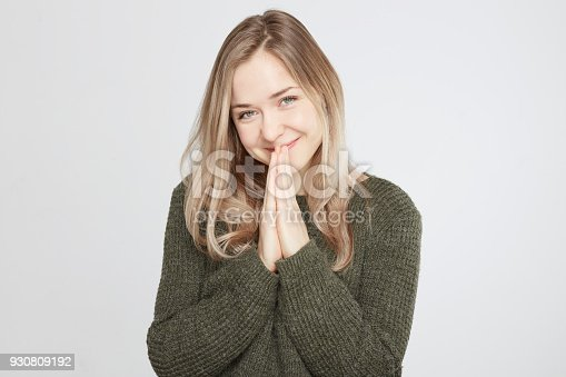 Beautiful pleased young female has broad smile, rouge cheeks, closes eyes and keeps palms together, being in anticipation of something important for her, isolated over white studio background.