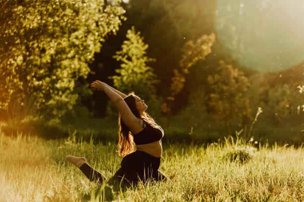 menina mais bonita do tamanho que faz a ioga na natureza em um dia de verão ensolarado. - body positive - fotografias e filmes do acervo