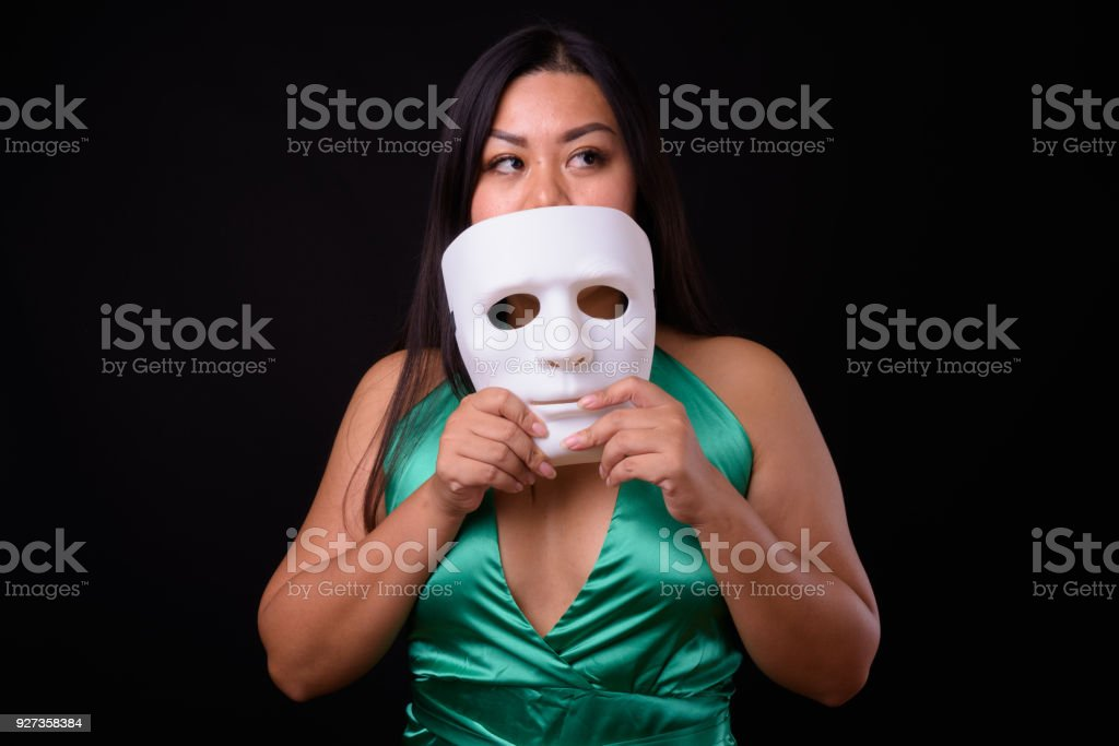 Beautiful Plus Size Woman Model Holding White Mask Against Black Background - Royalty-free 25-29 Years Stock Photo