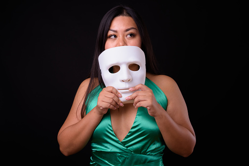 Beautiful Plus Size Woman Model Holding White Mask Against Black Background Stock Photo - Download Image Now