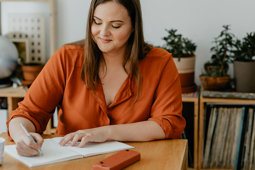 A smiling plus size woman sitting at her desk and writing a journal.
