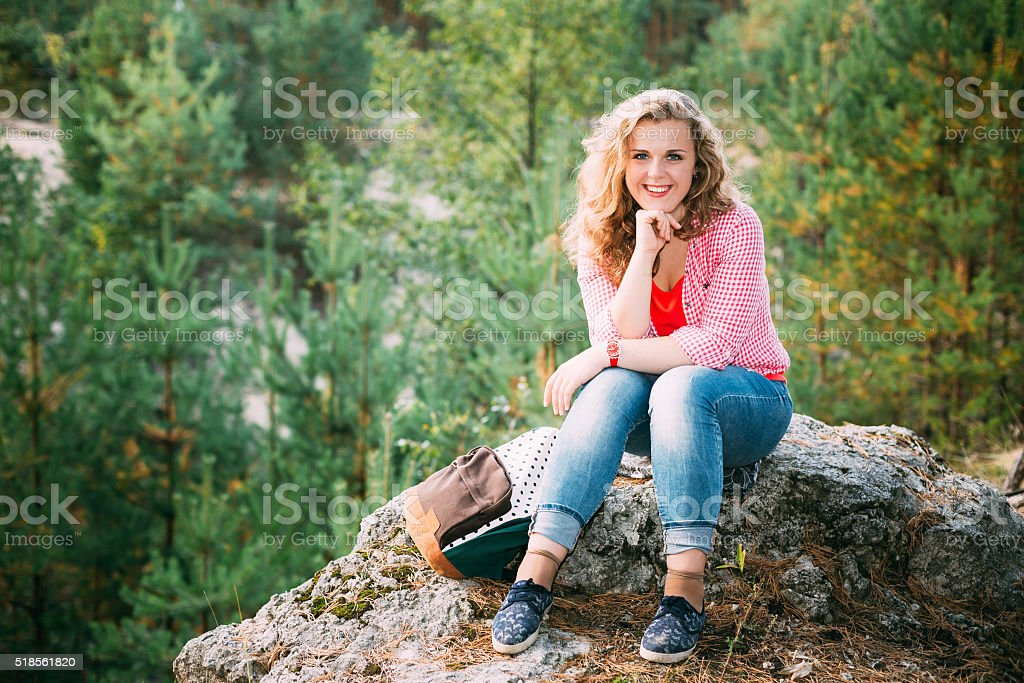 Beautiful Plus Size Young Smiling Woman Sitting on Stone inSumme stock photo