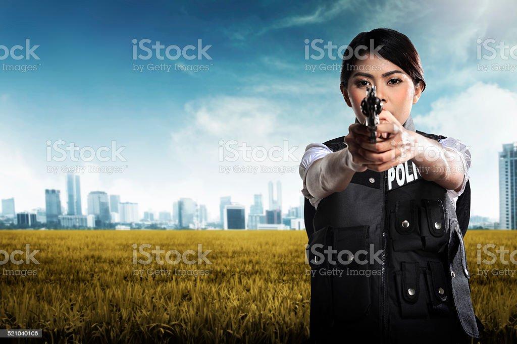 Beautiful police woman holding gun stock photo