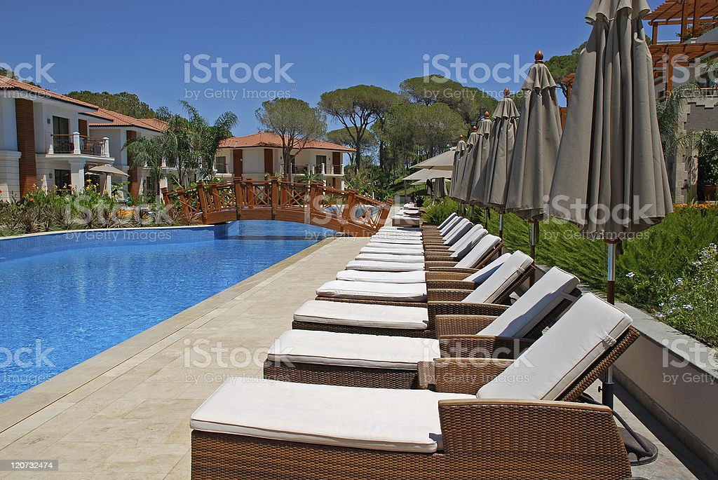 Beautiful poolside with line of chaise longues royalty-free stock photo