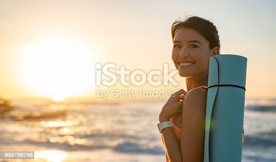 Beautiful portrait of a woman doing yoga outdoors and enjoying the sunrise at the beach and looking at the camera smiling
