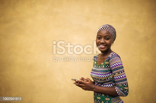 istock Beautiful portrait of a young African girl on her mobile phone Girl power 1002041512