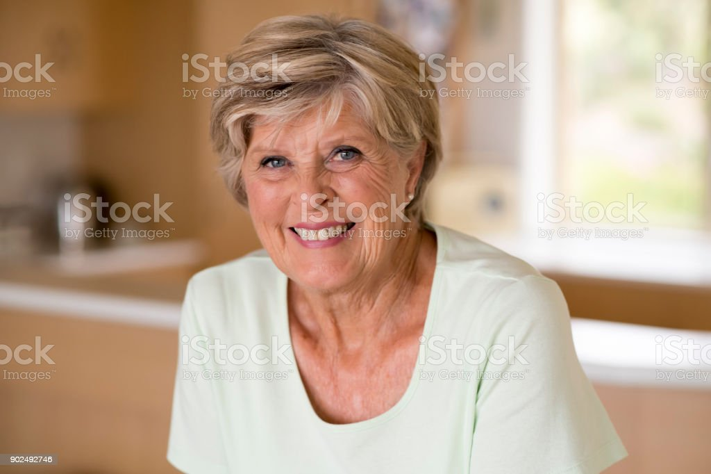 beautiful portrait of pretty and sweet senior mature woman in middle age around 70 years old smiling happy and friendly at home kitchen in aging and lifestyle concept stock photo