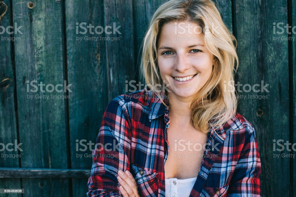 Beautiful portrait of young woman against wooden background stock photo