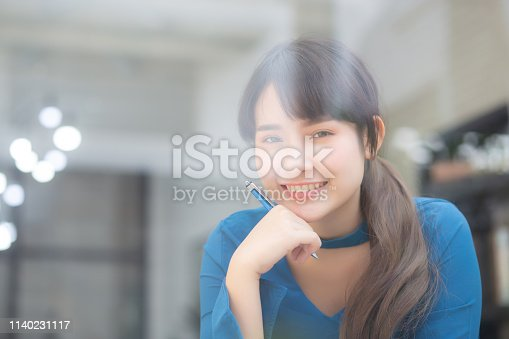 istock Beautiful portrait young asian woman writer smiling thinking idea and writing on notebook or diary with happy, lifestyle of asian girl is student, female planning working, education and business concept. 1140231117
