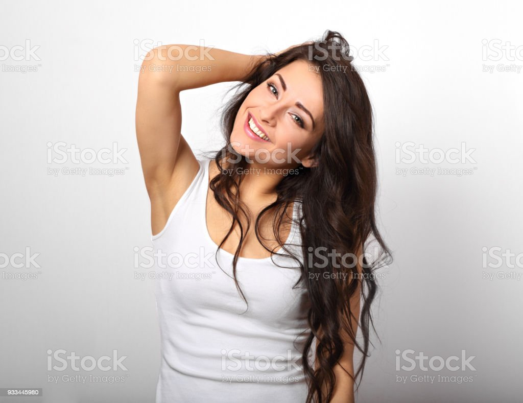 Beautiful positive fun happy woman in white shirt with toothy smile showing her epilation armpit on white background stock photo