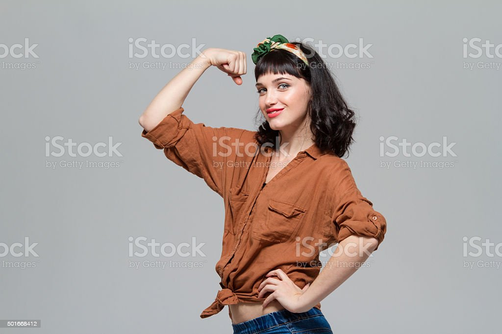 Beautiful positive happy young woman showing biceps stock photo