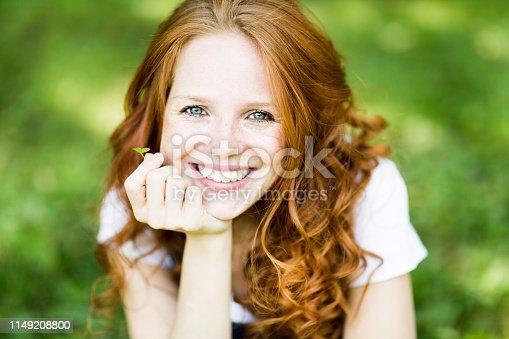 junge schöne frau mit schönem lächeln, roten haaren, blauen augen, sommersprossen, glücksklee, jeanshose, freizeit,urlaub,erholen,freudig,freude