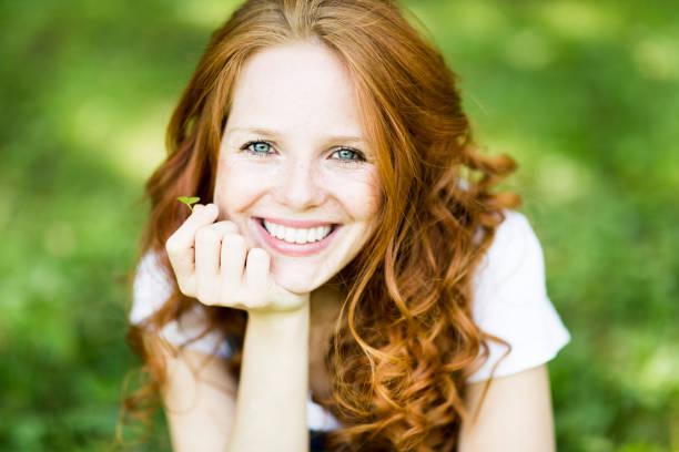belle jeune femme rousse positive avec les yeux bleus dans la nature - sourire à pleines dents photos et images de collection