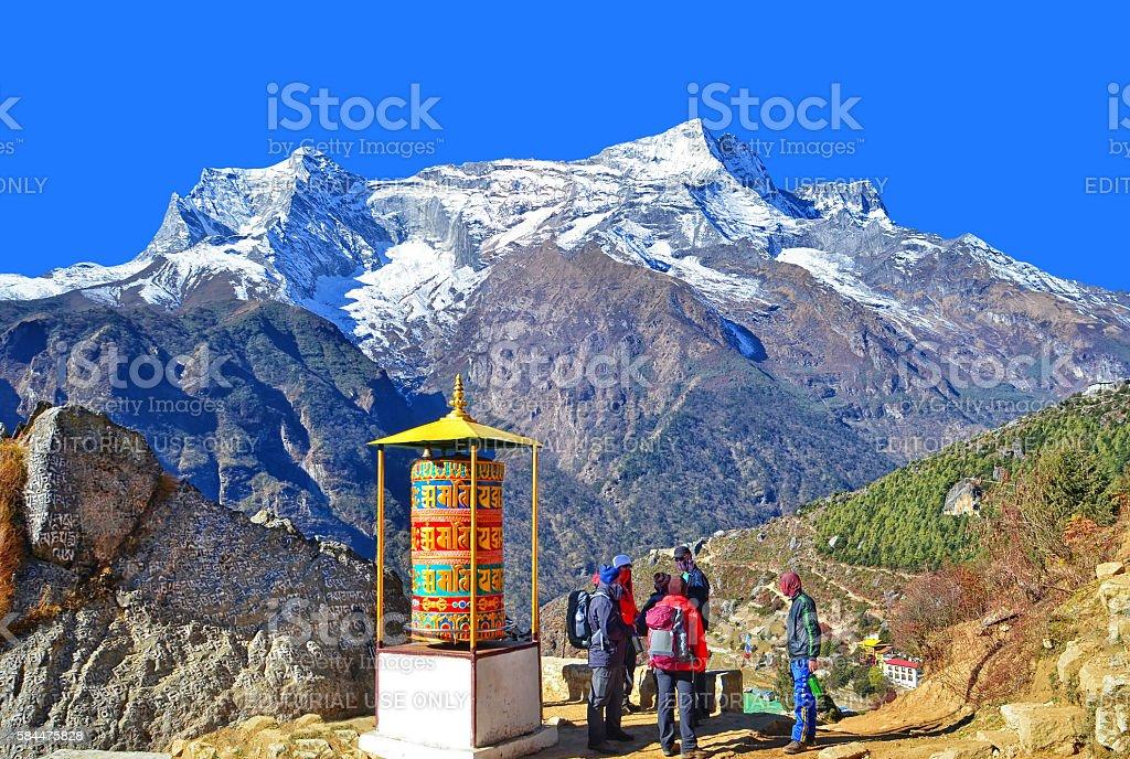Beautiful prayer wheel and hikers in Himalayan region stock photo