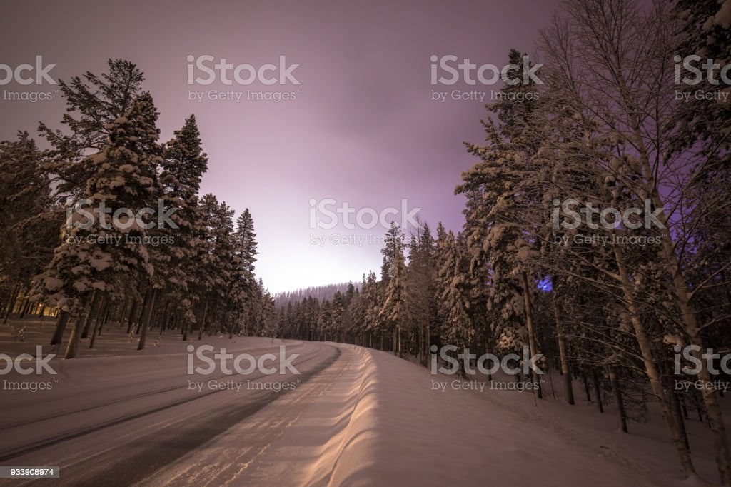 Beautiful pre dawn sky illuminates snow covered road in Finland stock photo