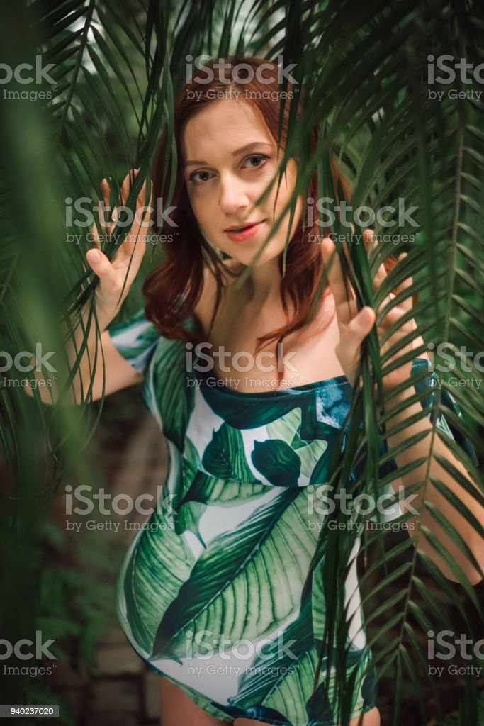 4021e8041100c Beautiful pregnant caucasian redhead woman in swimsuit in palm royalty-free  stock photo