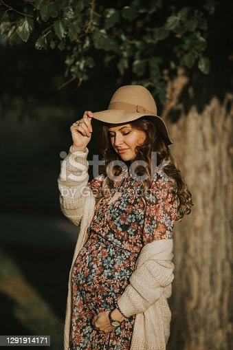 Beautiful pregnant girl with cowboy hat wearing dress with flowers
