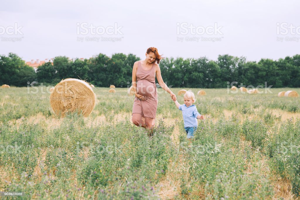 Beautiful pregnant woman and her cute toddler son having fun on wheat field with haystacks at summer day on nature, outdoors. stock photo