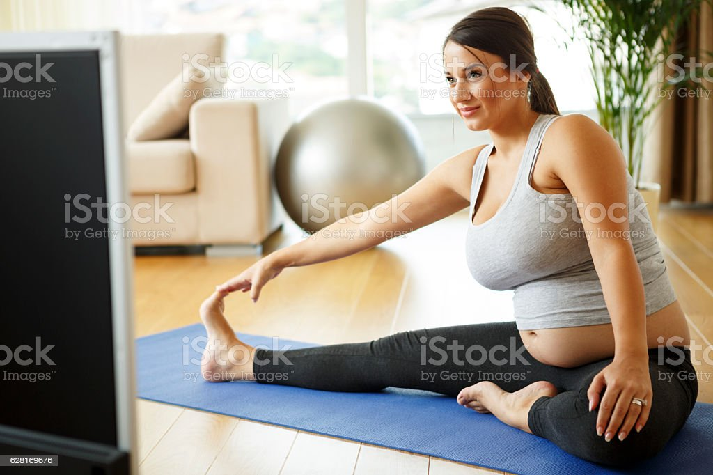 Beautiful pregnant woman exercising by watching television stock photo