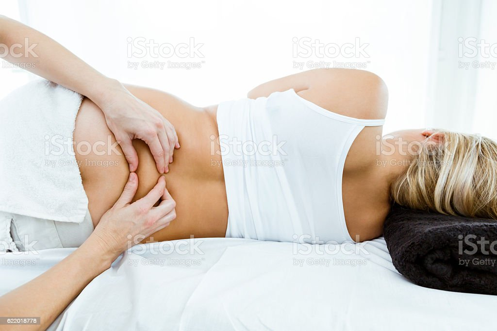 Beautiful pregnant woman having a massage in spa. stock photo