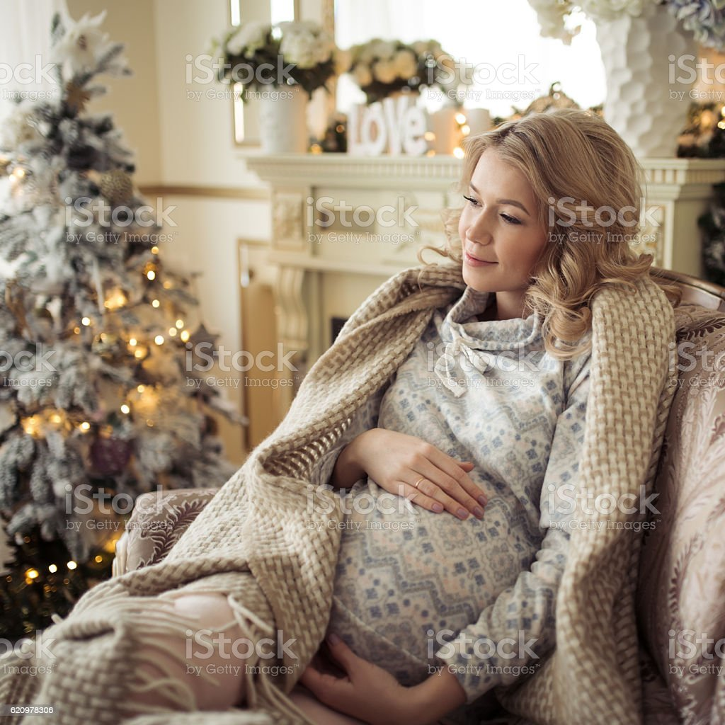 Beautiful Pregnant Woman In A Chair Near The Christmas Tree. foto royalty-free