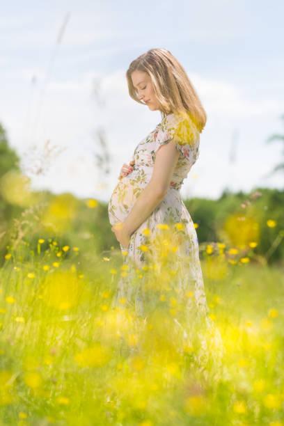 Schöne schwangere Frau in weißem Sommerkleid auf Wiese voller gelb blühender Blüten. – Foto
