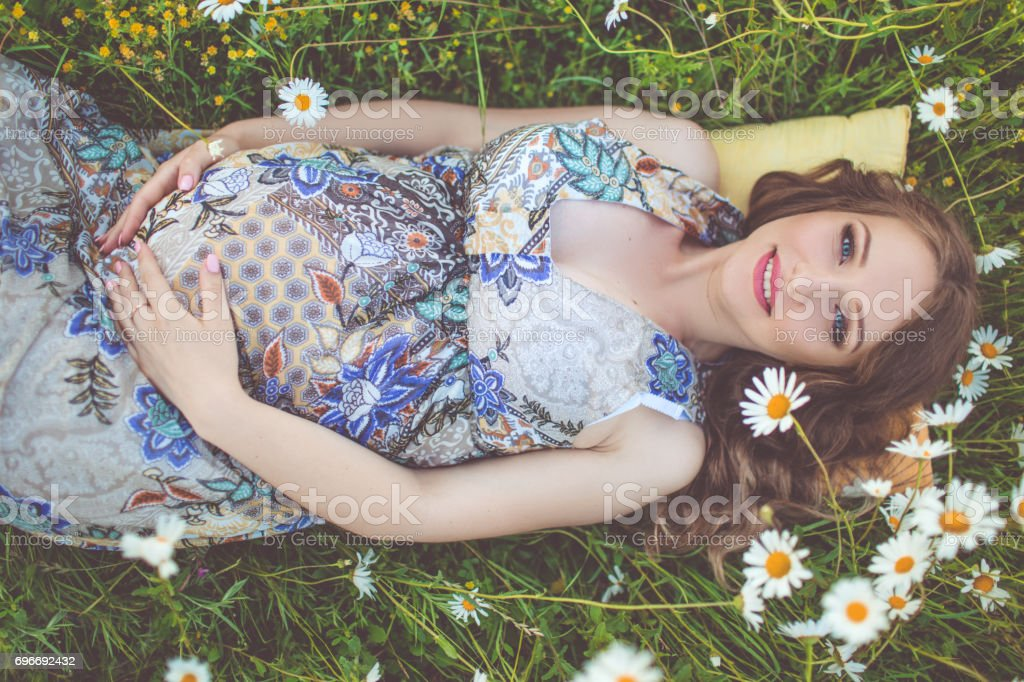 Beautiful pregnant woman lying in the camomile field stock photo
