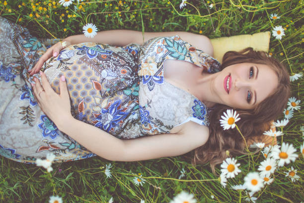 beautiful pregnant woman lying in the camomile field - makeup for pregnant women stock photos and pictures