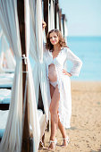 Beautiful pregnant woman on the beach dressed a white bikini and beach pareo