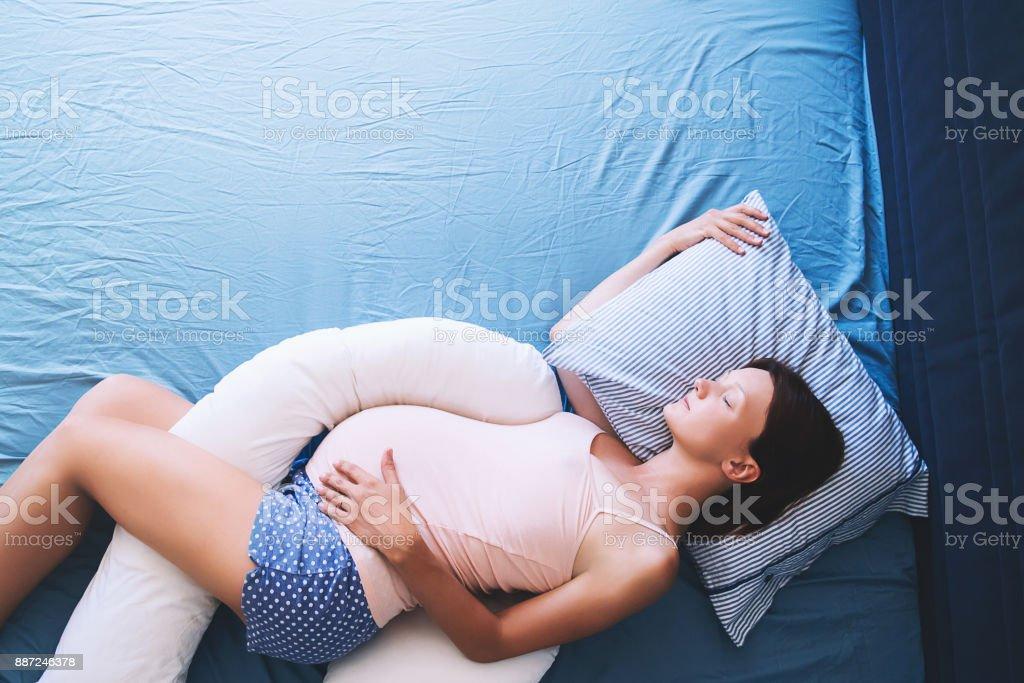 Hermosa mujer embarazada relajarse o dormir con la barriga apoyar la almohada en la cama. - foto de stock