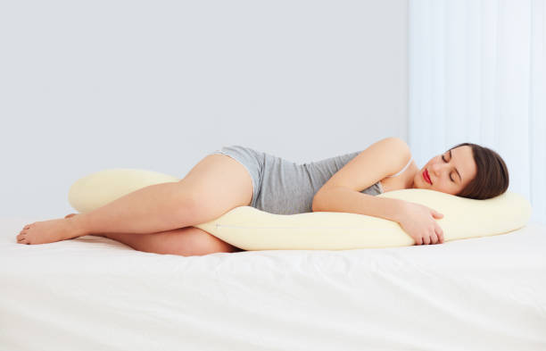 beautiful pregnant woman sleeps comfortable with tummy supporting pillow stock photo