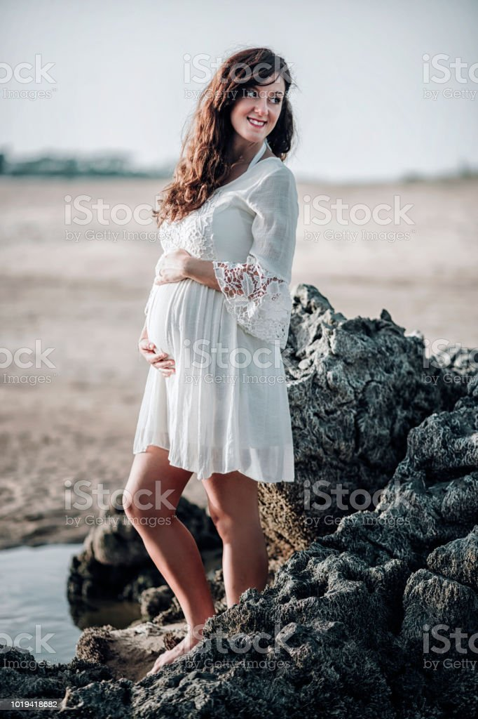 4f748d1c8bad2 Beautiful Pregnant Woman Standing On The Beach Stock Photo & More ...