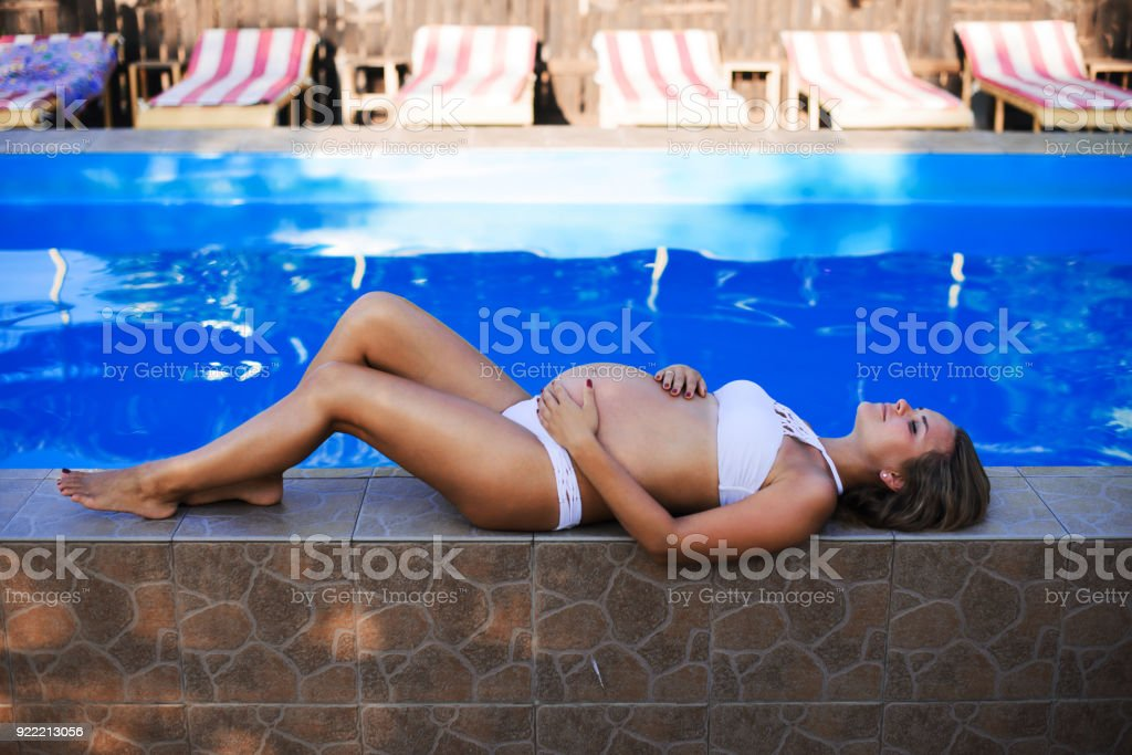 f1d35750335e2 Beautiful pregnant woman sun tanning relaxed at blue pool with green bikini  - Stock image .