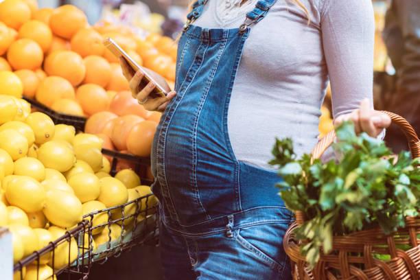 schöne schwangere frau mit smartphone auf dem lebensmittelmarkt - latzhose für schwangere stock-fotos und bilder