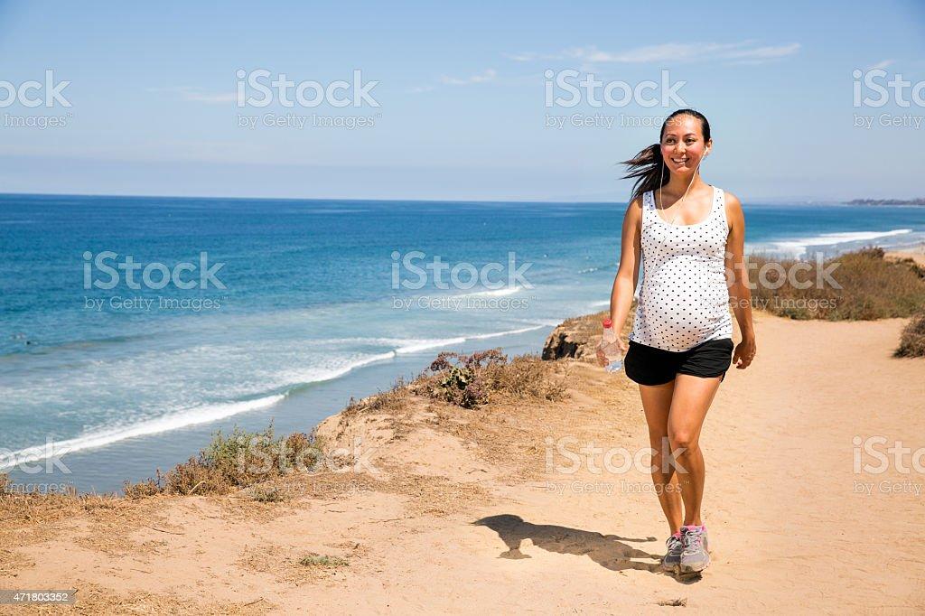 Beautiful pregnant woman walking along the coast stock photo