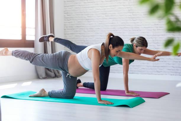 Schöne schwangere Frau mit ihrem Physiotherapeuten tun Pilates Übungen Vorbereitung für die Geburt. – Foto