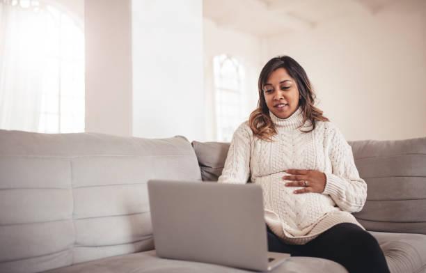 schöne schwangere frau mit laptop auf dem sofa sitzen - schwanger werden rechner stock-fotos und bilder