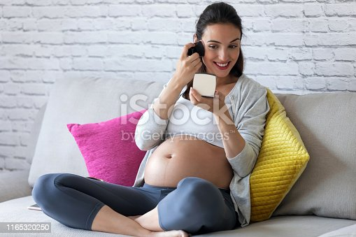 Shot of beautiful pregnant young woman doing her makeup while sitting on sofa at home.