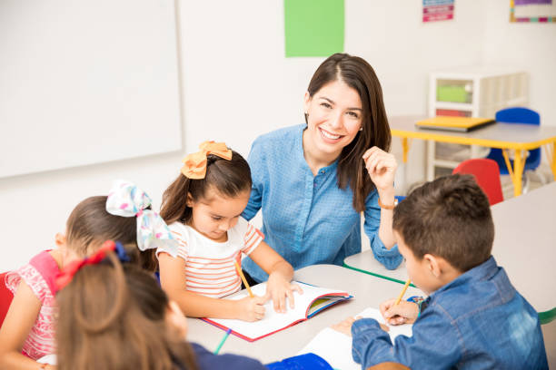 Beautiful preschool teacher during class Portrait of a gorgeous Hispanic preschool teacher teaching her students in a classroom elementary age stock pictures, royalty-free photos & images
