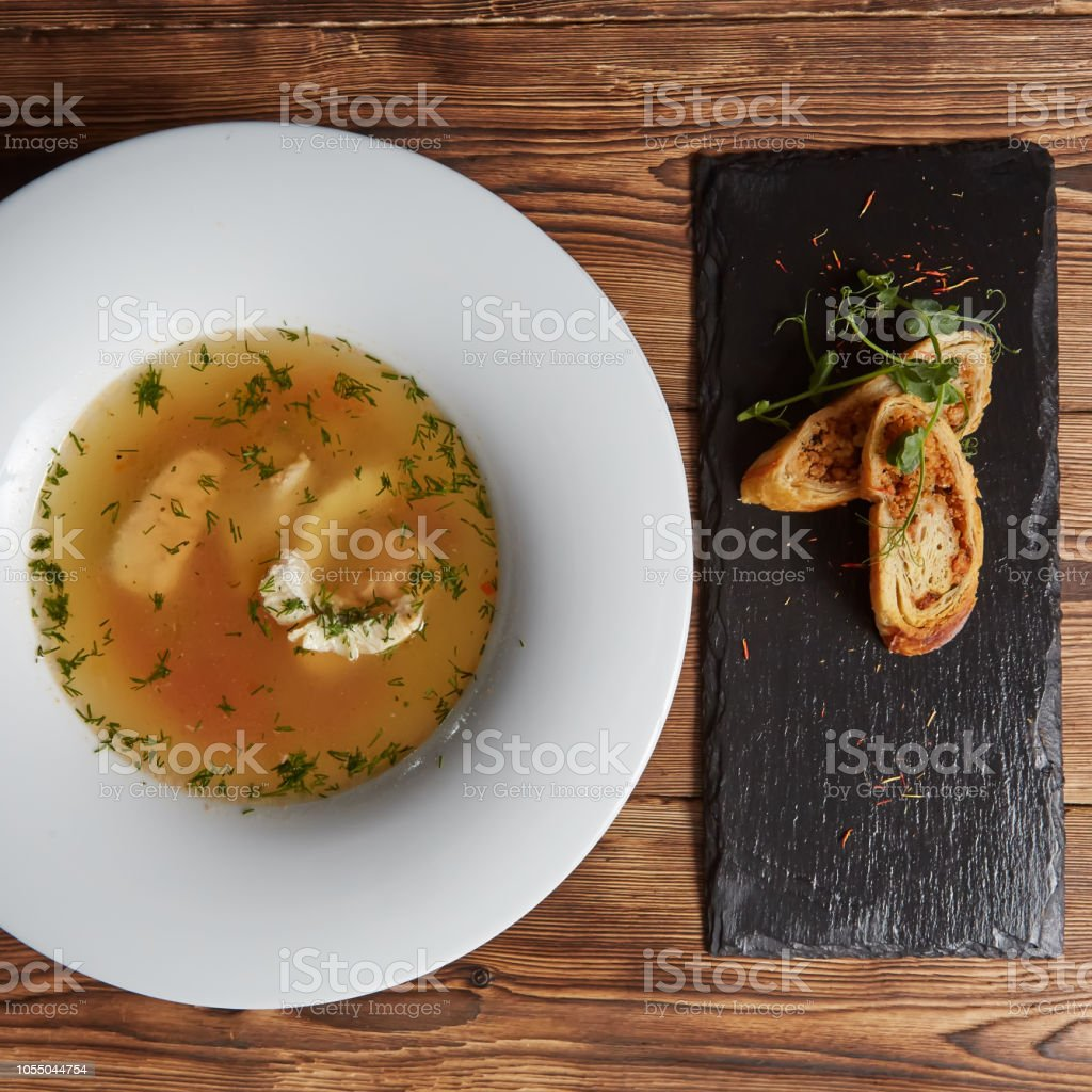 Beautiful presentation of the fish soup in a white plate, with bread...