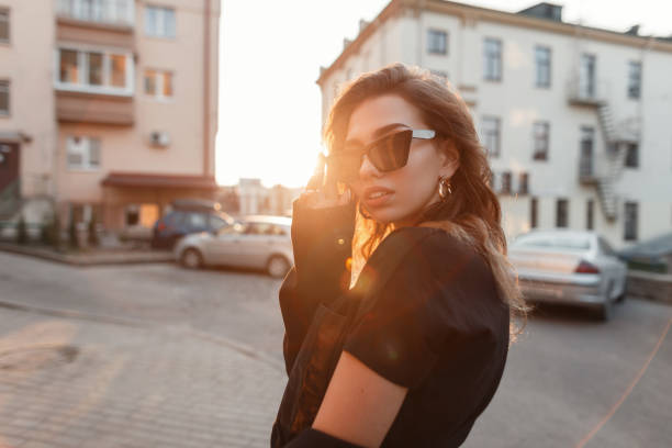 Beautiful pretty young hipster woman in trendy clothes in retro style in fashionable dark sunglasses is posing outdoors in the city on a sunny spring warm day. Urban girl fashion model. stock photo