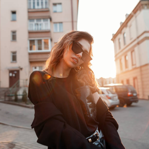 Beautiful pretty young hipster woman in trendy clothes in retro style in fashionable dark sunglasses is posing outdoors in the city on a sunny spring warm day. Urban attractive girl fashion model. stock photo