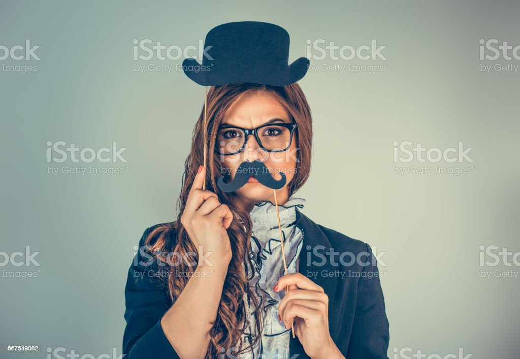 Beautiful, pretty young woman imitating upset man. Attractive girl holding paper mustache hat isolated on gray green background. Close up portrait headshot. Positive human emotions, facial expressions stock photo